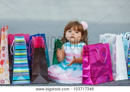 little girl and lots of colorful bags