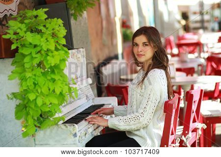 Romantic Girl Playing On An Old Piano In Street Cafe