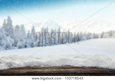 Winter background with pile of snow and blur landscape. Empty wooden planks on foreground. Copyspace for text