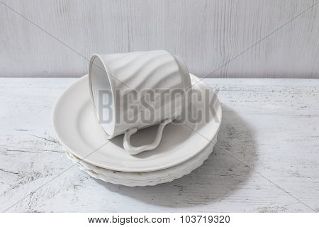 stack of white plates and cup on wooden white table