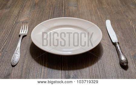 antique fork, knife and plate on wooden table
