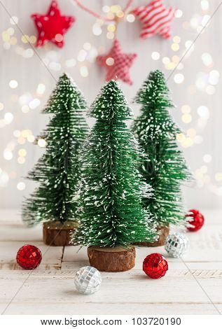 Three decorative Christmas tree on the white wooden background