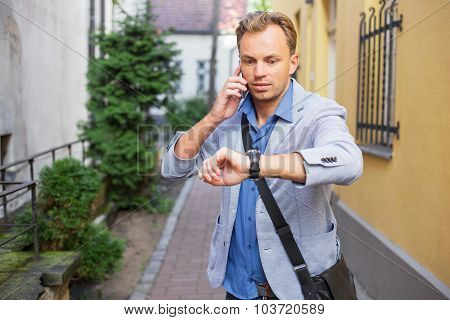 Man checking time on his watch and talking on the phone