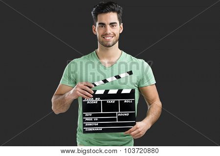 Portrait of handsome young man holding a clapboard, isolated on gray background