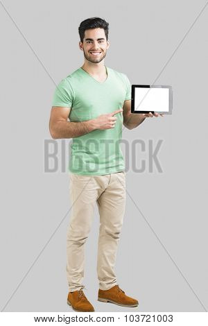 Handsome young man showing something on a tablet, isolated over gray background