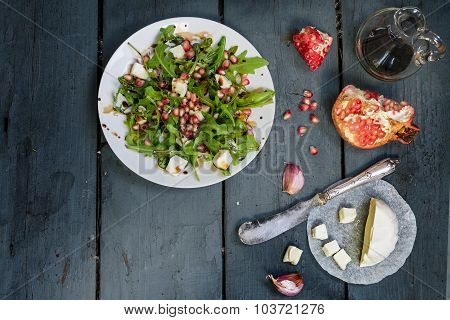 Salad With Arugula, Feta Cheese And Pomegranate On  Rustic Wood