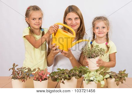 Mother And Two Daughters Caring For Potted Flowers