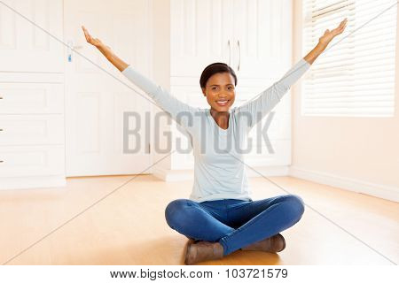 happy young african woman sitting on wooden floor with arms up