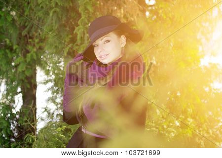 Winter woman on background of winter landscape, sun. Fashion girl in forest wonderland. Winter sunset scene. Model in sunlight, backlight