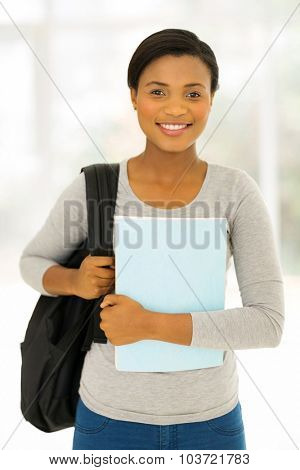 attractive female afro american student holding a book at home