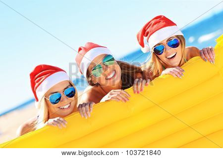 A picture of a group of women in bikini and Santa's hats holding mattress on the beach