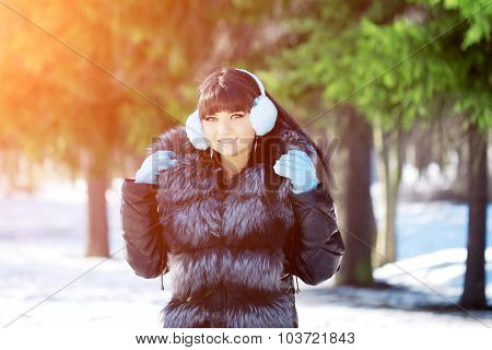 Winter woman on background of winter landscape sun. Fashion girl in forest wonderland. Winter sunset scene. Model in sunlight, backlight