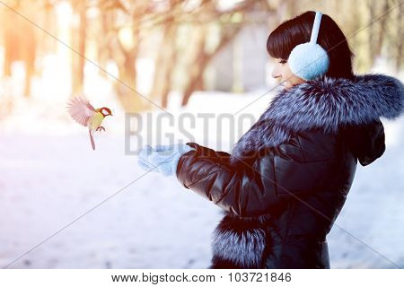 Young woman feeding birds in the winter forest Winter woman on background of winter landscape? sun. Fashion girl in forest wonderland. Winter sunset scene. Model in sunlight, backlight