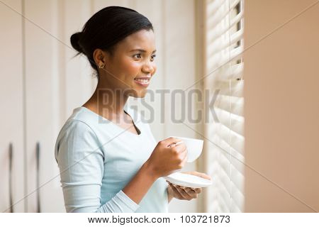 attractive african woman drinking coffee near the window at home