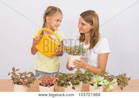 Happy Mother And Daughter Looking At Each Other Watering Flowers
