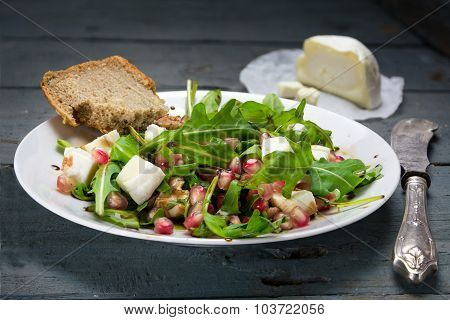 Arugula Salad With Cheese Served On A White Plate On Rustic Wood