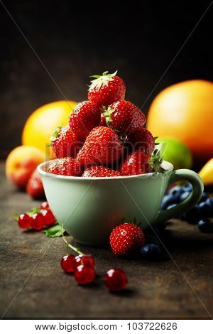 Strawberries in a cup and fresh fruits on rustic background