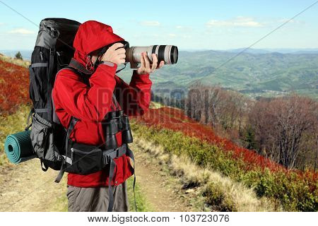 Tourist In A Red Jacket With A Gray Backpack Taking Pictures