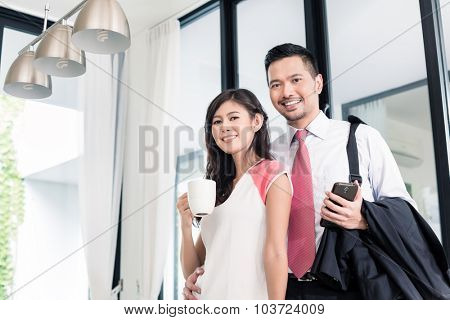 Asian couple having breakfast before man goes to office, standing in their home