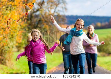 Family take walk in autumn forest flying kite