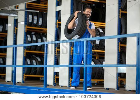 Auto mechanic carrying tire in tire store