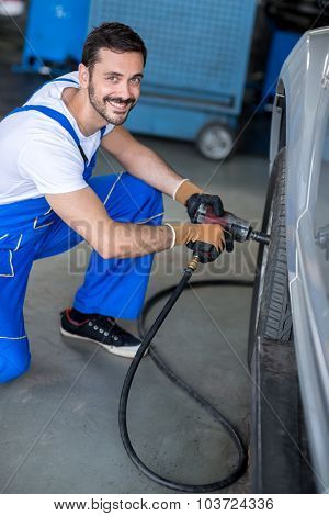 smiling mechanic repairing car wheel in workshop with wrench
