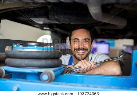 Satisfied male mechanic under car