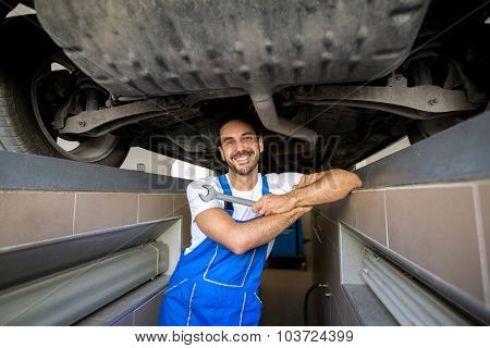Portrait of male mechanic underneath a car