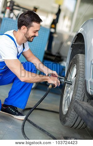 Auto mechanic changing tyre on car with pneumatic wrench