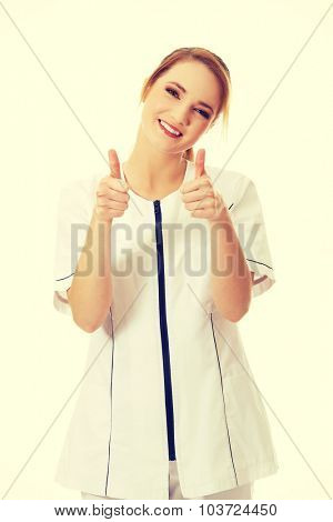 Young female doctor or nurse with thumbs up.