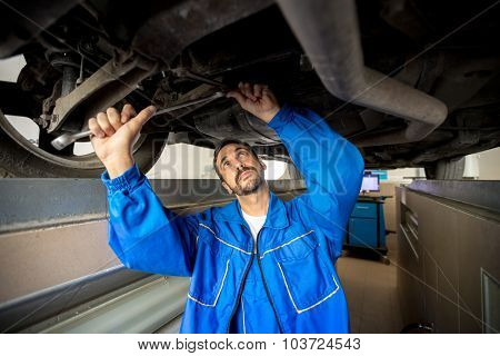 A mechanic is checking the technical state underneath a car