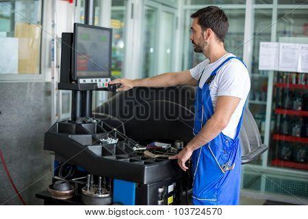 Mechanic working on balancing machine at the garage