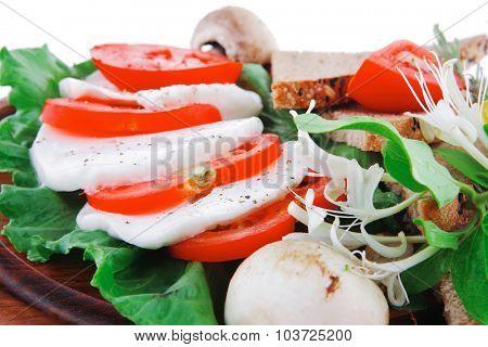 mozzarella and tomato slices on wooden plate
