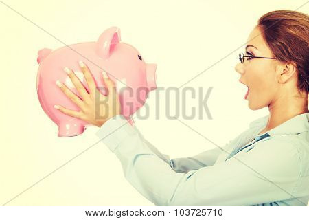 Shocked business woman holding piggy bank.