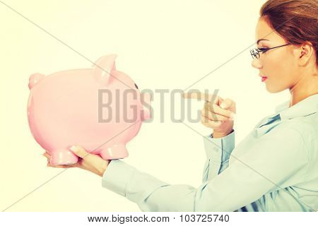 Beautiful business woman pointing on piggy bank.