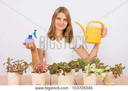 The Girl Is Holding A Spray Bottle And A Watering Can To Care For Flowers