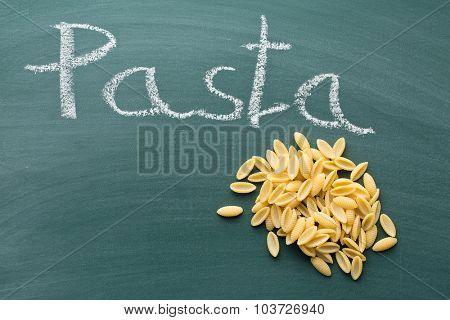 uncooked italian pasta on green chalkboard