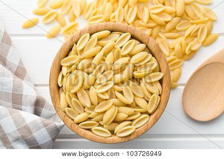 uncooked italian pasta in wooden bowl on kitchen table