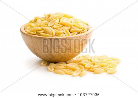 uncooked italian pasta in wooden bowl on white background