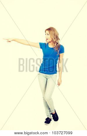 Beautiful young casual woman pointing aside.