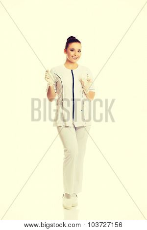 Smiling female nurse holding a drip.