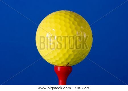 Yellow Golf Ball On Red Tee Against Blue Background