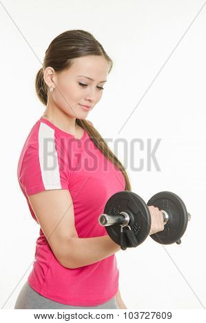 Girl Athlete Is Looking At Dumbbell In Hand