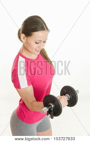 Sportswoman Looking At Dumbbell In The Right Hand