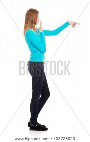 Shocked teenage woman pointing to the left