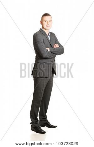 Confident young businessman with folded arms.