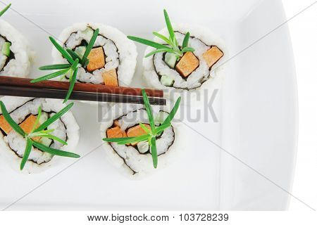 Maki Sushi - California Roll with Cucumber , Cream Cheese and Raw Salmon inside. Served with wasabi and ginger . on long white plate isolated over white background