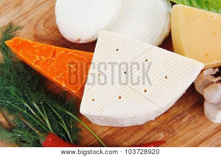 several soft and hard types of french cheese on wooden board with hot peppers and dill isolated on white background