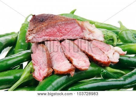 meaty food : roasted red meat steak sliced on a green hot chili peppers on a white back