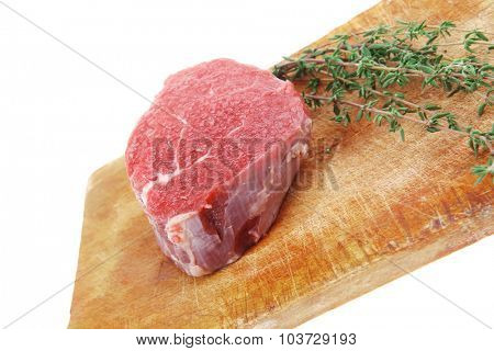 red fresh fillet chops : raw beef fillet on wooden board with thyme ready to prepare . isolated over white background